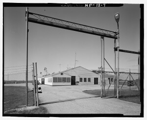 """Entrance to Oscar-Zero Launch Control Facility (U.S. Government public domain image) The image above is a photo taken after the base was closed, prior to its re-opening as a historic site….the boarded-up windows are now uncovered. Note the """"high security"""" chain link fence to keep unwanted visitors off the property…but I suppose when your front door is 41/2 feet thick and located 60 feet underground, a wimpy property fence isn't your only safeguard against unwanted visitors….."""